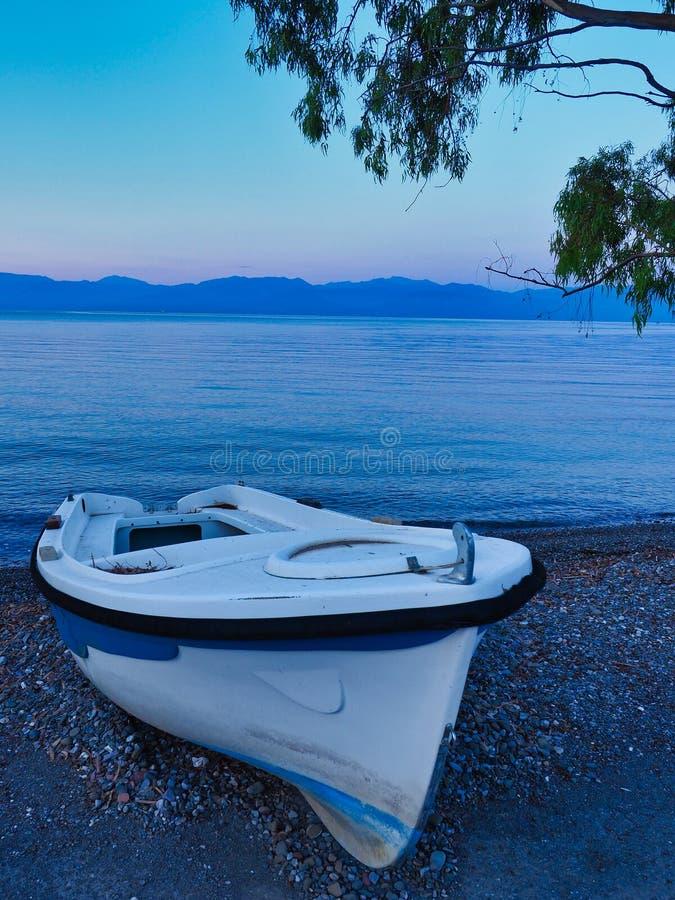 在圆石滩的小白色渔船在黎明,希腊 免版税库存图片