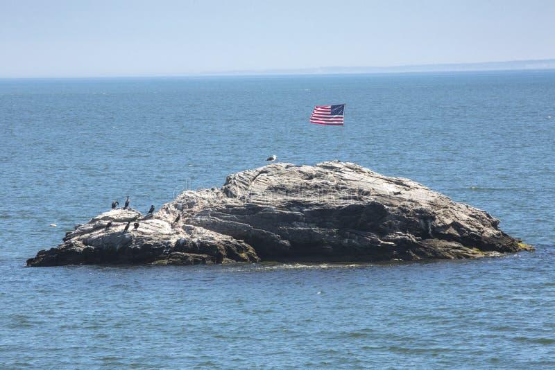 在圆锥形小屋岩石的美国国旗在Niantic海湾,康涅狄格 免版税库存照片