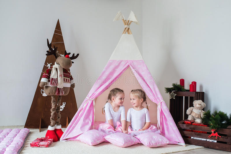 在圆锥形帐蓬的两个小女孩戏剧 库存图片