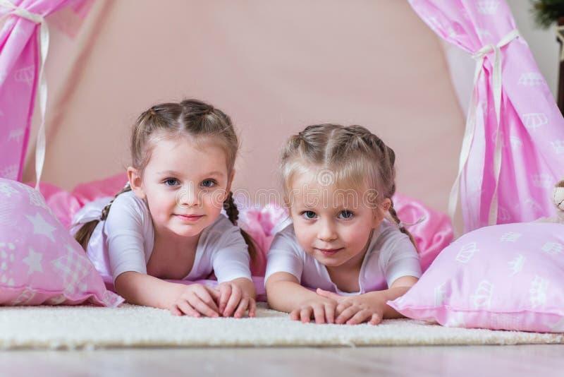 在圆锥形帐蓬的两个小女孩戏剧 免版税图库摄影