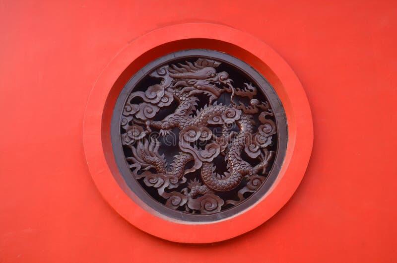 在圈子的木被雕刻的龙在中国佛教寺庙的红色背景在蓝毗尼,尼泊尔 免版税图库摄影