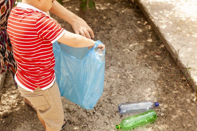 在土地的塑料污染 收集塑料瓶的小男孩 孩子运载垃圾袋 ?? 免版税库存图片