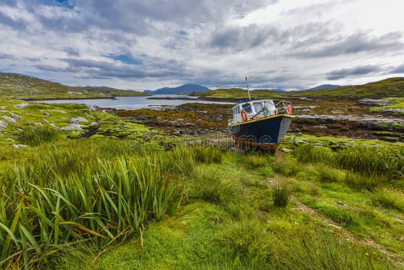 在土地的渔船在一个入口前面的一个美丽如画的环境里处于低潮中在哈里斯和Lew `小岛的风景  免版税库存照片
