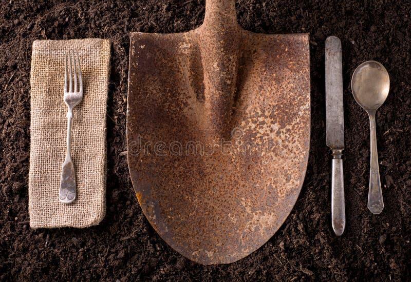 在土壤背景的生锈的铁锹与叉子、刀子、匙子和na 免版税库存照片