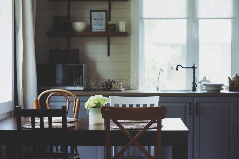 在土气乡间别墅厨房的舒适夏天早晨 与鲜花花束,开放棚架的木桌 免版税库存图片