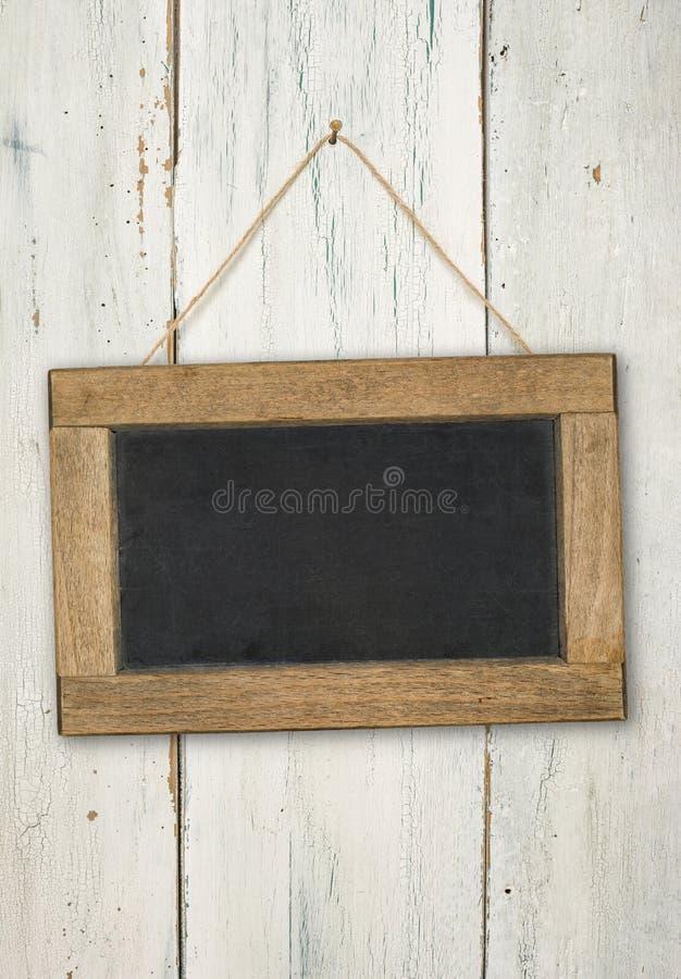 在土气木墙壁上的空的黑板 免版税库存照片