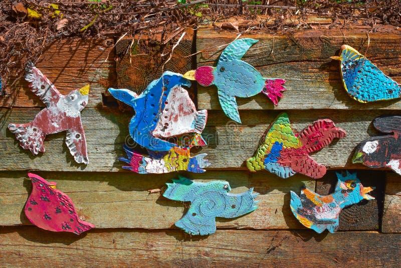 在土气木墙壁上的被绘的鸟 库存图片
