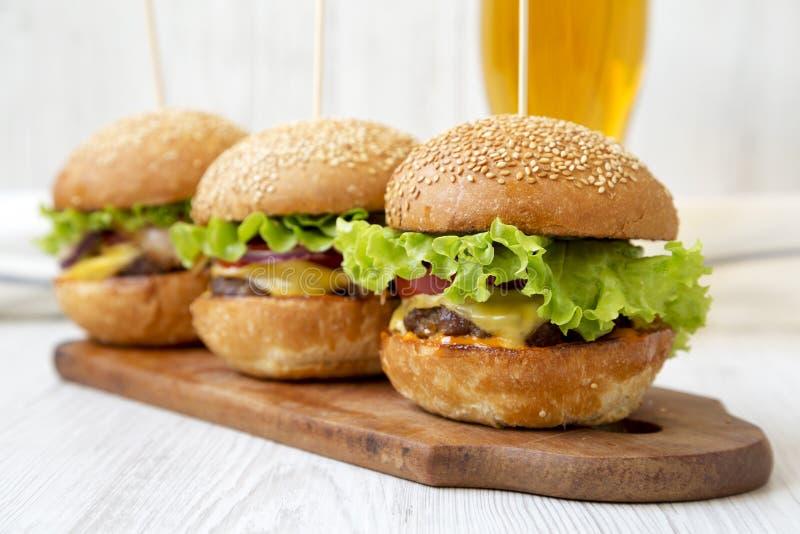 在土气木板和杯的自创乳酪汉堡冰镇啤酒,侧视图 r r 免版税库存图片