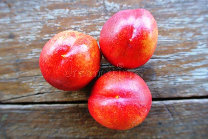 在土气木桌上的三个成熟红色油桃 免版税库存照片