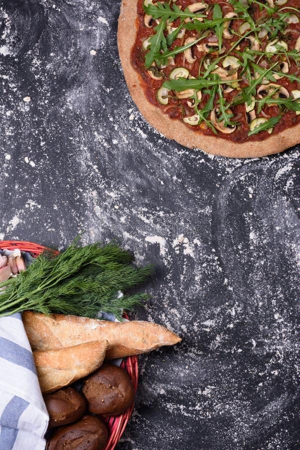 在土气木桌上的意大利薄饼和面包篮子 平的位置,拷贝空间 免版税库存图片