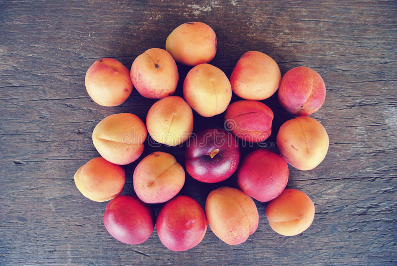 在土气木桌上的成熟橙色杏子 图库摄影
