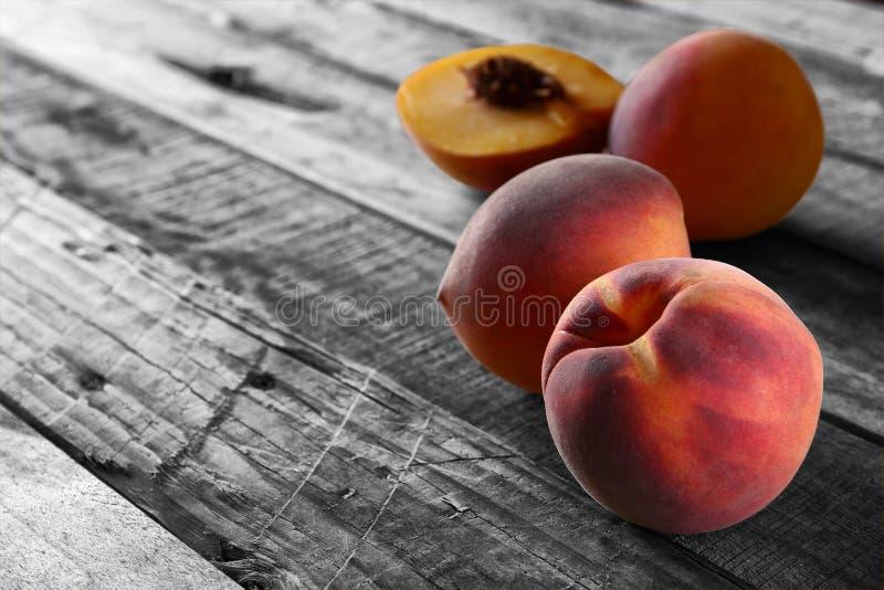 在土气木桌上的新鲜的甜桃子 有选择性的颜色 免版税库存图片