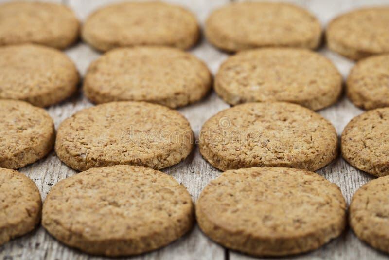 在土气木桌上的新鲜的被烘烤的燕麦曲奇饼特写镜头 免版税库存照片