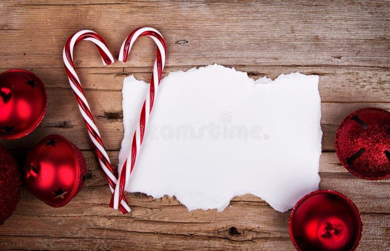 在土气木背景圣诞节装饰品的白色被撕毁的纸 库存图片