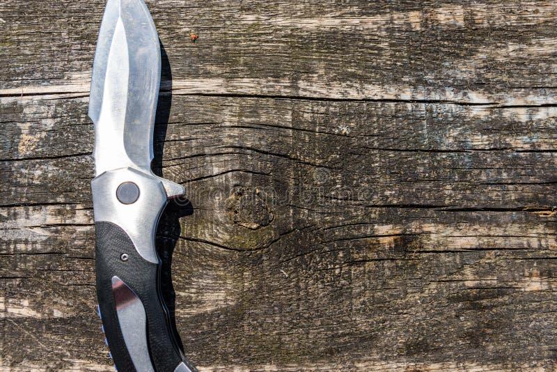 在土气木背景的折叠的刀子 库存照片
