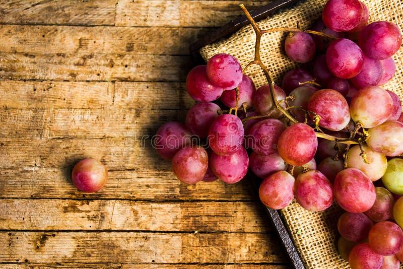 在土气木背景的新鲜的葡萄 库存照片