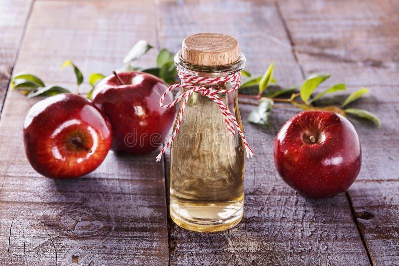 在土气木背景的苹果汁醋 免版税库存照片