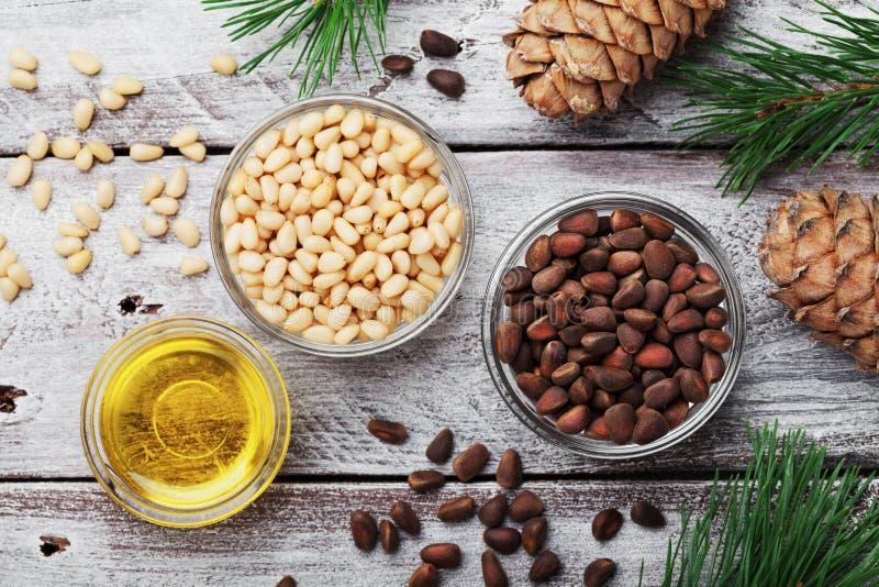 在土气木背景顶视图的松果、油和雪松锥体 有机和健康superfood 免版税库存照片