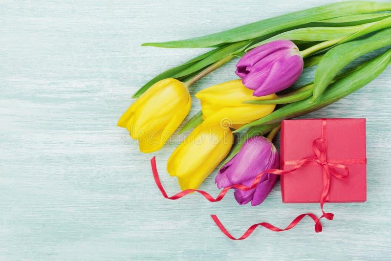 在土气桌上的礼物盒和郁金香花为3月8日,国际妇女天,生日或母亲节 免版税库存照片