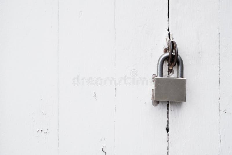 在土气白色困厄的木门的挂锁 免版税库存图片