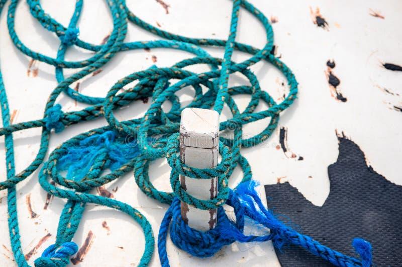 在土气白色小船摘要照片的蓝色滑车 在白色木头的土气蓝色绳索 白色游艇外部细节 免版税库存图片