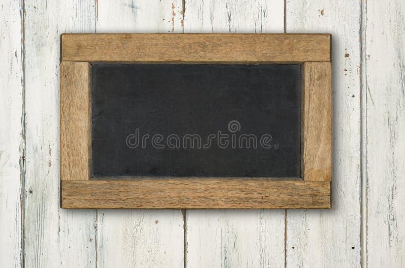 在土气白色木背景的黑板 免版税图库摄影