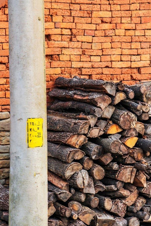 在土气砖篱芭和一个电线杆旁边的被堆积的木日志 图库摄影