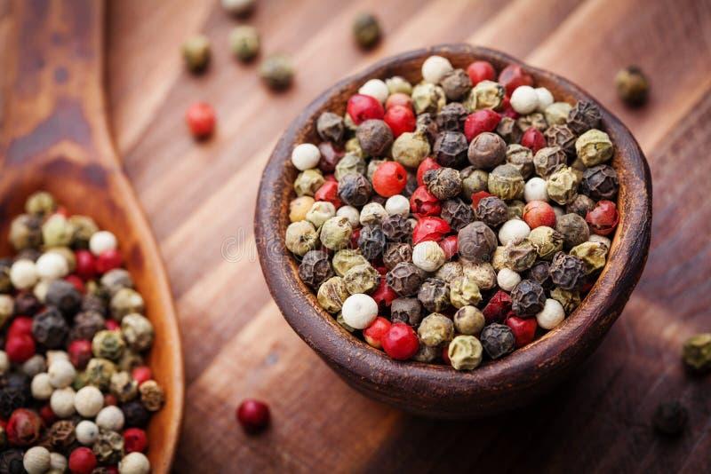 在土气碗的混杂的五颜六色的干胡椒在木桌上 宏观射击 免版税库存照片