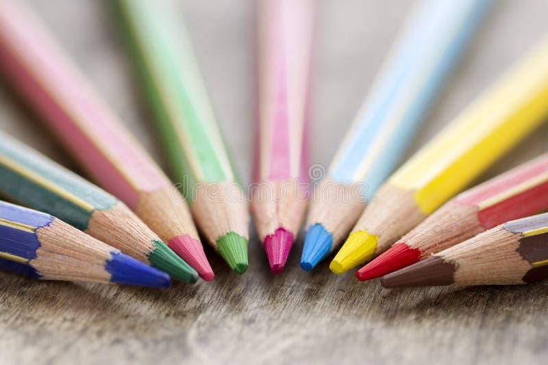 在土气背景的五颜六色的木颜色铅笔 库存照片
