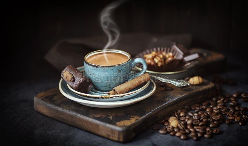 在土气背景的咖啡杯 浓咖啡用肉桂条、蓝色在一个老委员会的咖啡和咖啡豆,土气,黑暗 免版税库存图片