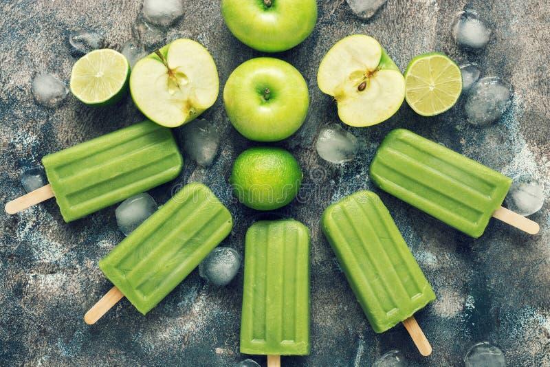 在土气背景的绿色冰棍儿用苹果和石灰 夏天刷新的点心 平的位置,看法从上面 被定调子的照片 免版税库存图片