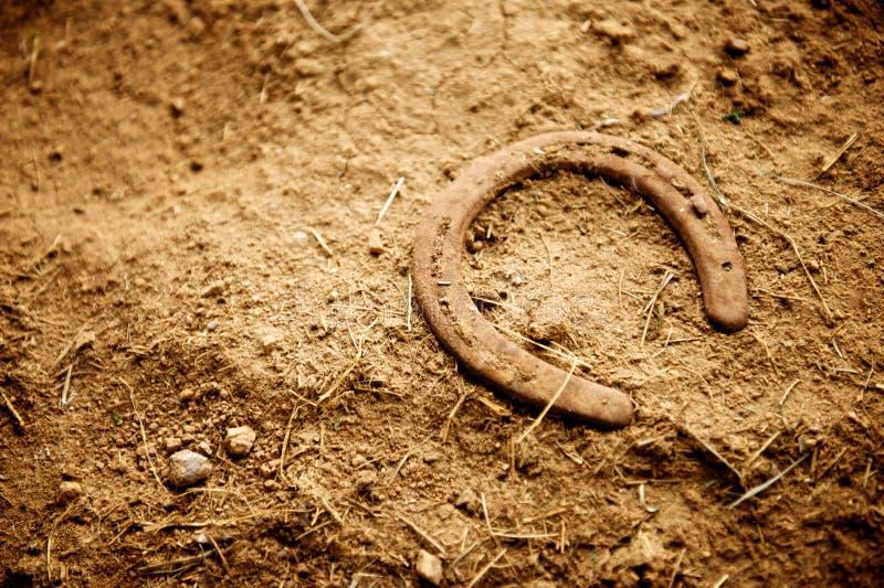 在土的生锈的老马鞋子 免版税库存照片