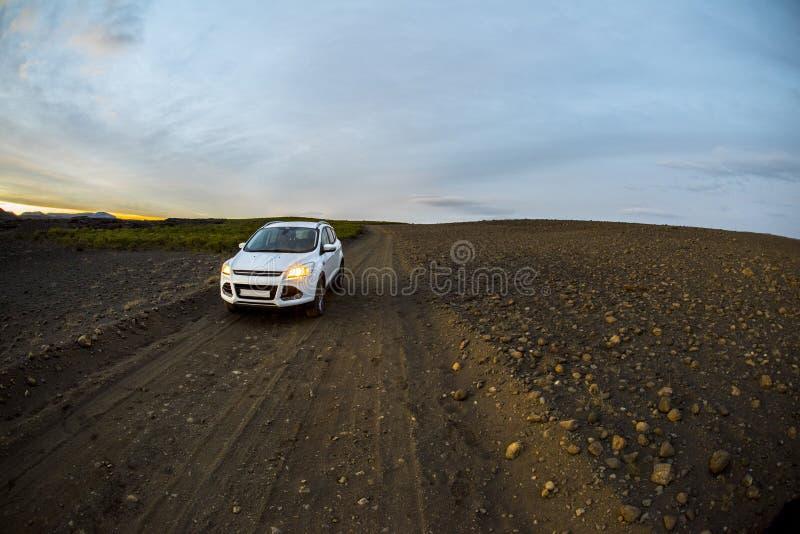 在土领域中间的汽车在黄昏附近日落的一条被铺平的路  免版税库存图片