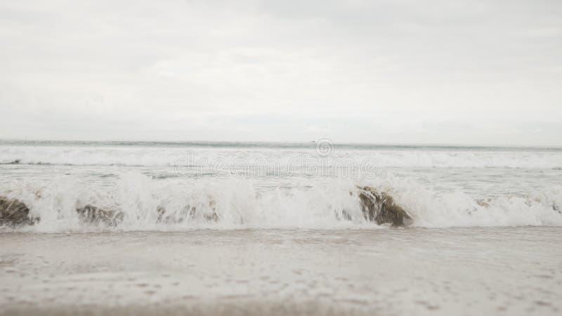 在圣塔蒙尼卡的小波浪在多云11月天靠岸 库存图片