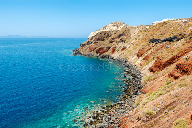 在圣托里尼海岛,希腊上的五颜六色的岩石岸 库存图片
