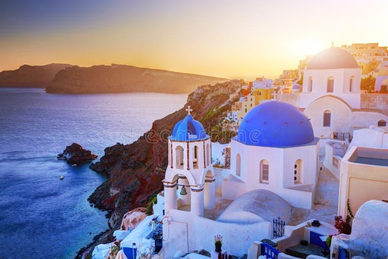 在圣托里尼海岛,日落的希腊上的Oia镇 在爱琴海的岩石 免版税库存图片