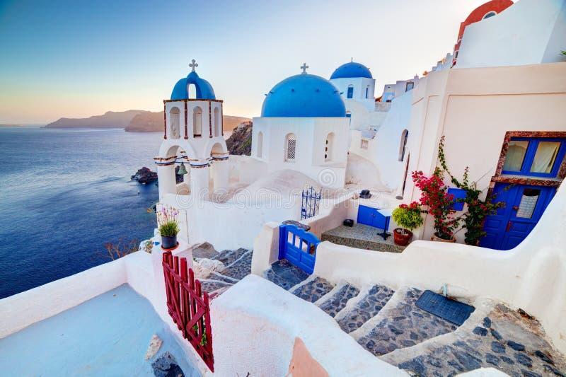 在圣托里尼海岛,日落的希腊上的Oia镇 在爱琴海的岩石 免版税图库摄影