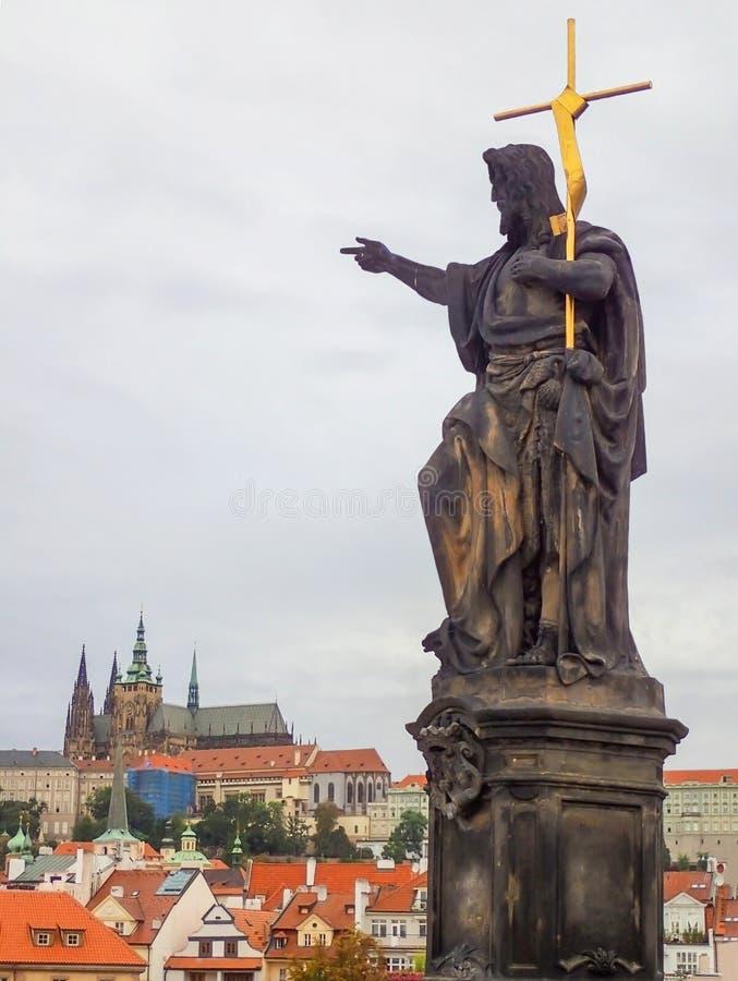 在圣查尔斯桥梁点的雕象在天际的城堡在Prag 免版税图库摄影