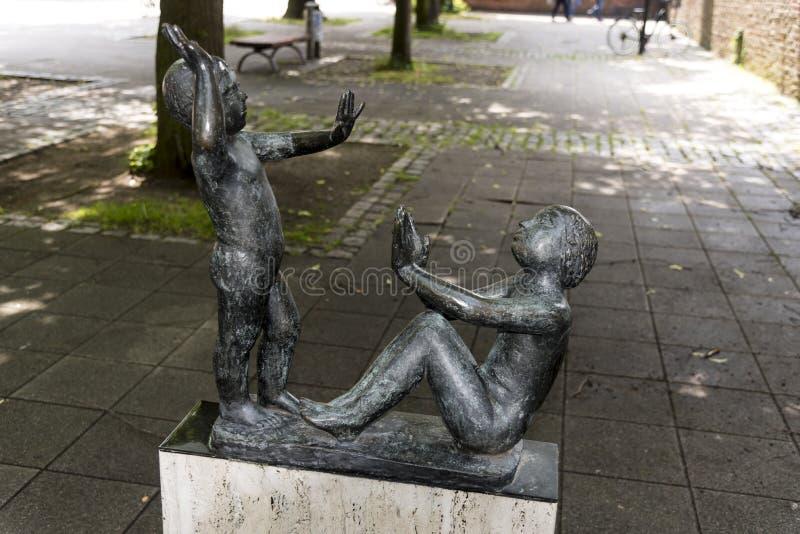 在圣玛丽的教会罗斯托克德国附近的Spielende更加亲切的使用的儿童雕象 免版税库存照片