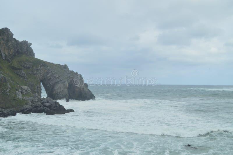 在圣胡安De Gaztelugatxe Here偏僻寺院的逃出克隆岛的岩石曲拱是王位被摄制的比赛  地质自然风景 免版税图库摄影