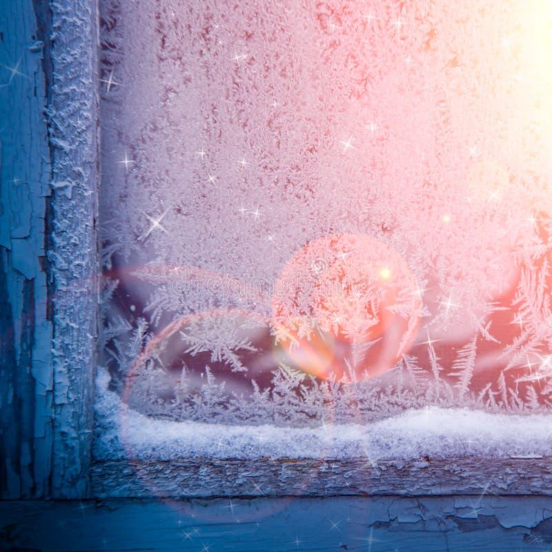 在圣诞前夕的冻玻璃窗 免版税库存图片