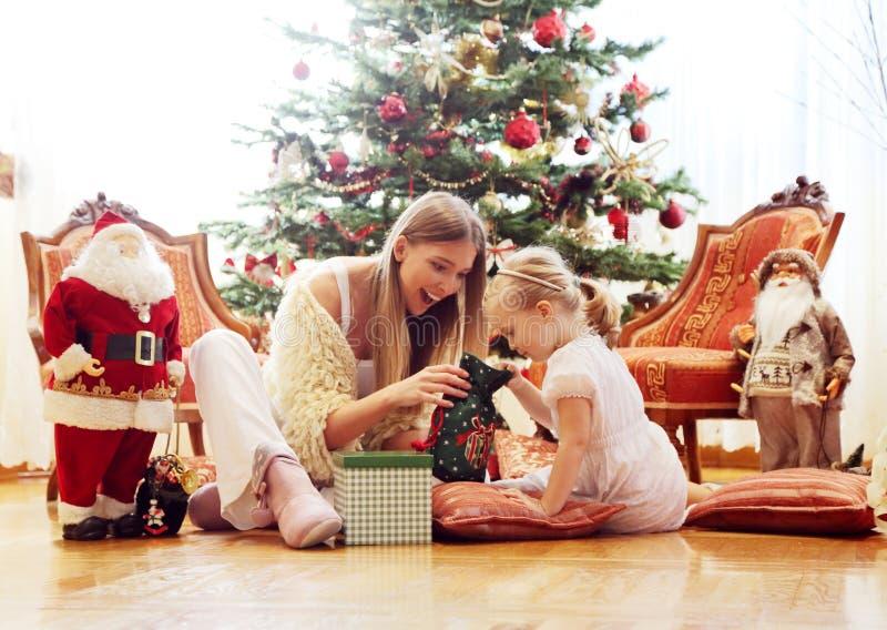 在圣诞树前面的妈妈和女儿选址 免版税库存图片