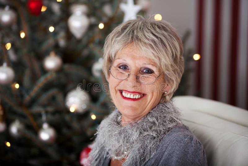 在圣诞树前面的微笑的资深夫人 免版税库存图片