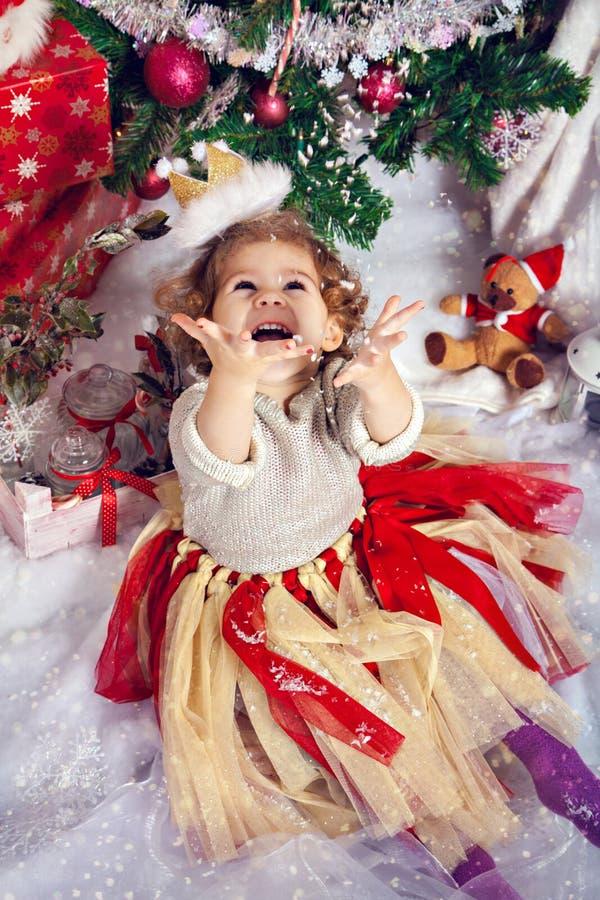 在圣诞树前面的愉快的小女孩 库存图片