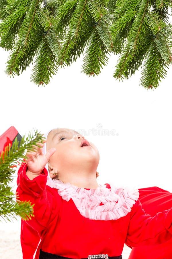 在圣诞树前面的美丽的女婴 免版税库存图片
