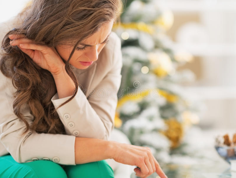 在圣诞树前面的被注重的少妇 免版税库存图片