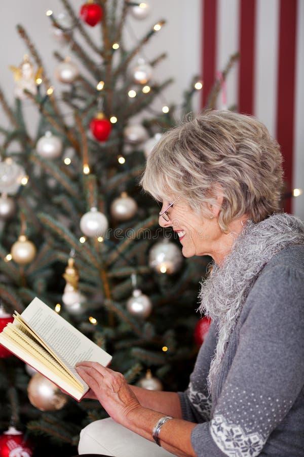 在圣诞树前面的资深夫人读书 图库摄影