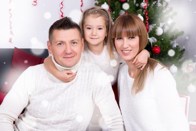 在圣诞树前面的年轻家庭 免版税图库摄影