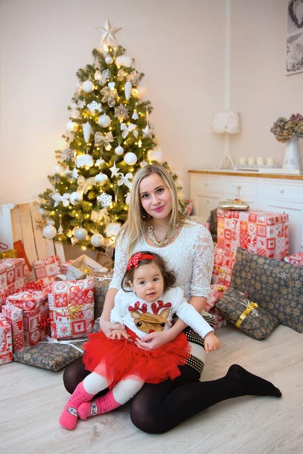 在圣诞树前面的年轻愉快的家庭 免版税库存图片