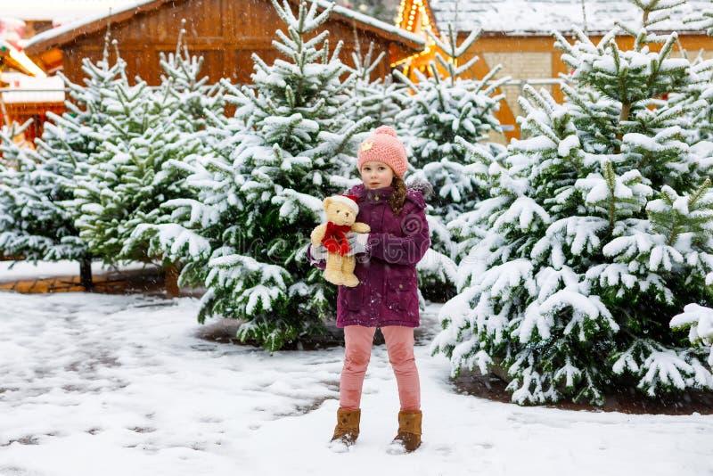 在圣诞树市场上的逗人喜爱的矮小的微笑的孩子女孩 选择在xmas的冬天衣裳和玩具的愉快的孩子xmas树 库存照片